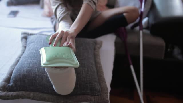 junge frau mit gebrochenem bein in orthopädischen guss zu hause - geduld stock-videos und b-roll-filmmaterial