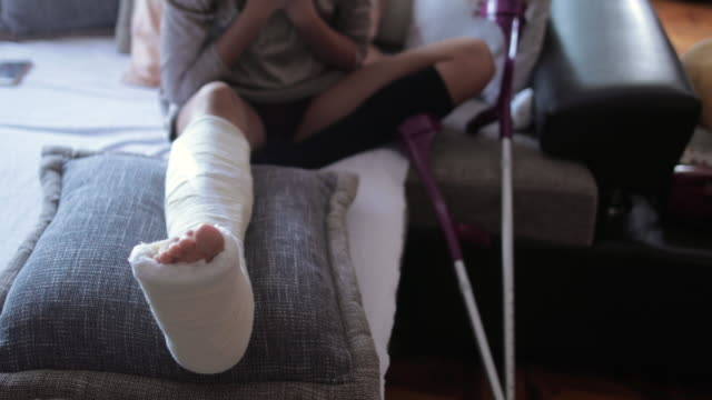 Young woman with broken leg in orthopedic cast at home