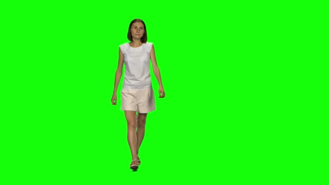 vídeos de stock e filmes b-roll de young woman with brown hair and smooth haircut is calmly walking on green screen. chroma key, 4k shot. front view - teeshirt template