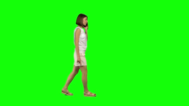 vídeos de stock e filmes b-roll de young woman with brown smooth haircut is calmly walking and talking on the mobile phone on green screen. profile view - teeshirt template