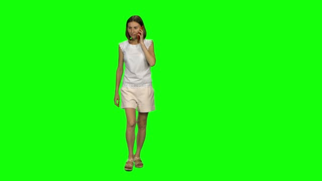vídeos de stock e filmes b-roll de young woman with brown smooth haircut is calmly walking and talking on the mobile phone on green screen. front view - teeshirt template