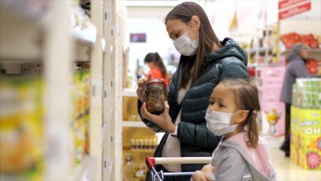 tıbbi maskeli çocuk kız ile genç kadın süpermarkette bir konserve yiyecek satın alır - maske stok videoları ve detay görüntü çekimi