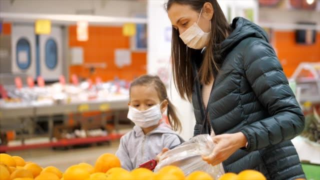 tıbbi maskeli çocuk kız ile genç kadın süpermarkette bir portakal satın alır - maske stok videoları ve detay görüntü çekimi