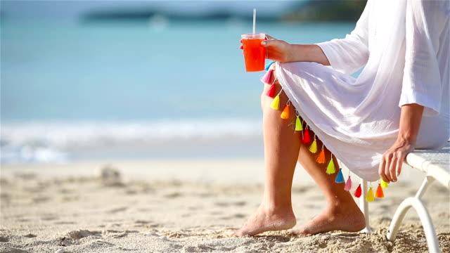 junge frau mit cocktailglas auf weißen strand auf der liege sitzen. closeup leckeren cocktail hintergrund das meer - sun chair stock-videos und b-roll-filmmaterial