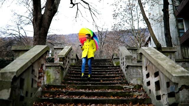 Joven con sombrilla color está parado en las escaleras - vídeo