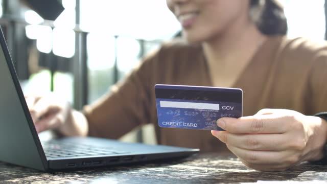 vídeos y material grabado en eventos de stock de mujer joven con tarjeta de crédito y computadora portátil de compras en línea en casa - shopping online