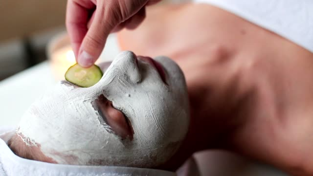 young woman with cucumber slices on the face in a spa saloon - cetriolo video stock e b–roll
