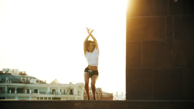 Video A young woman with curly hair and in small shorts performing attractive dancing - going down and spreading her legs - bright sunset