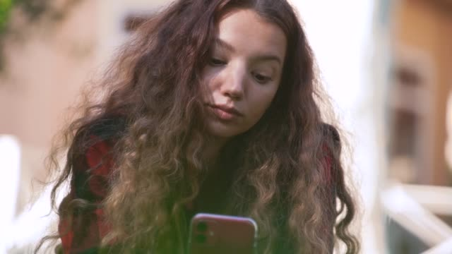 Young woman with curly hair looks into smartphone display