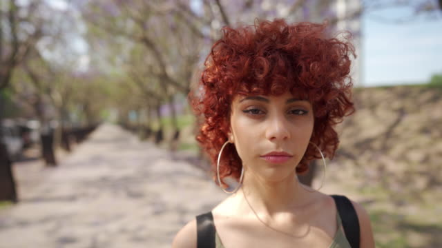 Young woman with curly red hair standing in park Portrait of young Latin woman with curly red hair standing in public park and looking at camera confidently dyed red hair stock videos & royalty-free footage