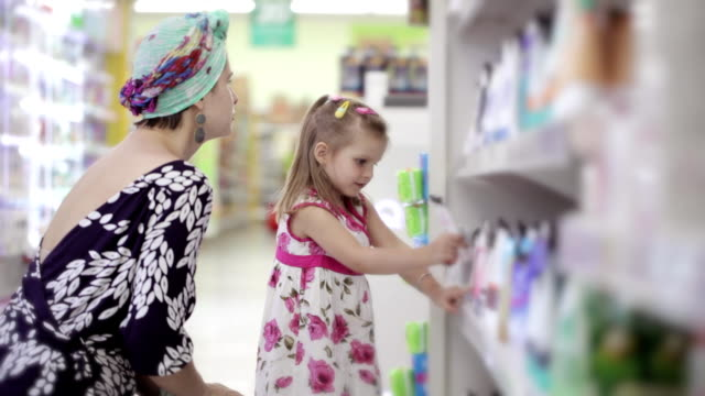 Young woman with daughter buying body care products in supermarket video