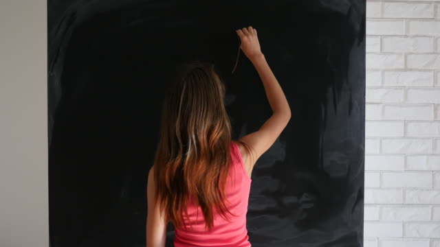 Young woman with devils horns drawn on blackboard standing and smirking at the camera video