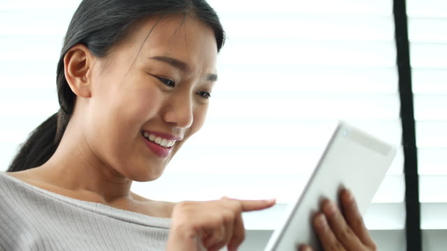 Young woman with digital tablet at home video