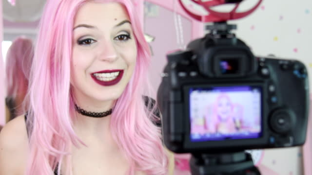 Young woman with dyed pink hair filming herself for social media video