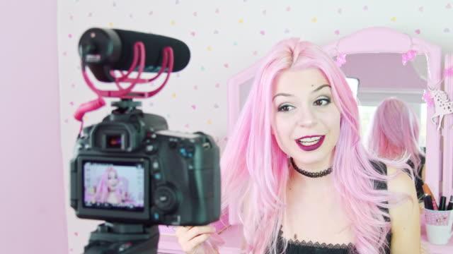 침실에서 비디오 카메라에 말하기 염색된 분홍색 머리를 가진 젊은 여자 - influencer 스톡 비디오 및 b-롤 화면