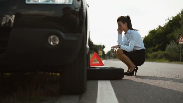 giovane donna con piatto auto pneumatici chiamate carro attrezzi - rimorchiatore video stock e b–roll