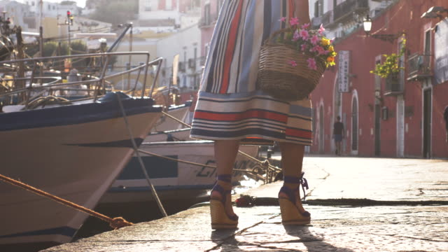 vídeos de stock e filmes b-roll de young woman with flower basket walking at seafront by the harbor in ponza island italy. fashion colorful dress skirt and hat. - saia