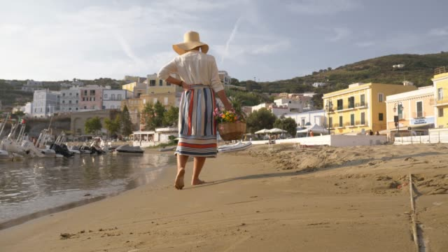young woman with flower basket walking barefoot at seafront on the beach by the harbor in ponza island italy. fashion colorful dress skirt and hat. - sardegna video stock e b–roll