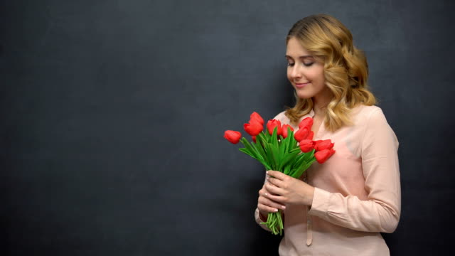 Young woman with flowers standing near blackboard, celebrating teachers day
