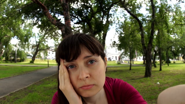 Young woman with headache doing selfie sitting on a bench in the park video