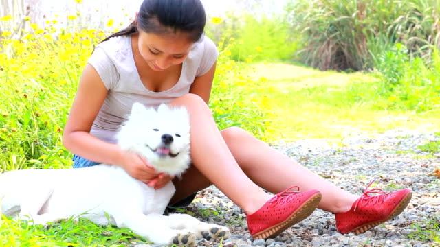 vídeos de stock e filmes b-roll de jovem mulher com seu cão - samoiedo