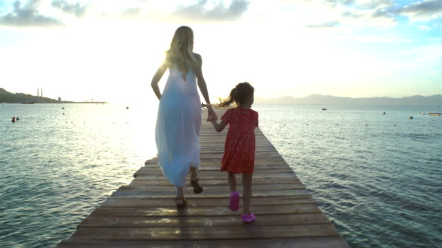 Young woman with her Little daughter running on a sea pier towards the rising sun Young woman with her Little daughter running on a wooden sea pier towards the rising sun jetty stock videos & royalty-free footage