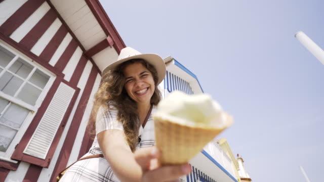 vídeos de stock e filmes b-roll de young woman with ice cream near striped buildings - aveiro