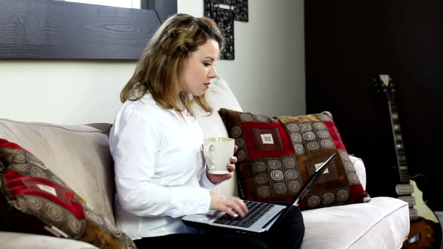 Young woman with laptop and coffee cup video