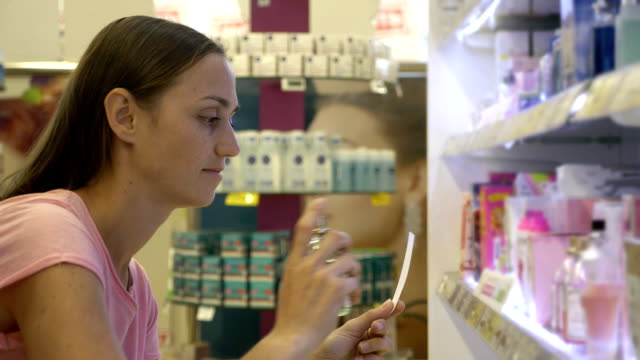 Young woman with ldaughter choosing perfume at beauty department of supermarket video