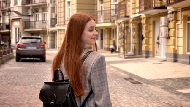 stockvideo's en b-roll-footage met jonge vrouw met lang gember haar lopen op straat en terugkijkend, holding rugzak, stedelijke straat achtergrond, achteraanzicht - men blazer