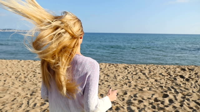 Young woman with long hair running at the beach