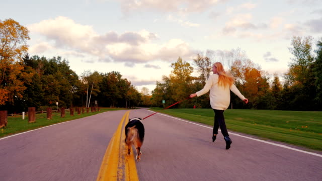 Young woman with long hair running with his dog on the road in the park. Keep a leash on the Australian Shepherd video