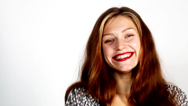 young woman with long reddish hair and red lipstick is looking at camera and smiling - sorriso aperto video stock e b–roll