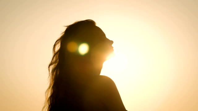 young woman with long wavy hair is wearing in summer dress is standing against the sun in evening time video