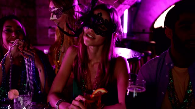Young woman with mask drinking cocktails at Mardi Gras party Young beautiful woman with mask and beads drinking cocktails and celebrating Mardi Gras at bar mardi gras stock videos & royalty-free footage