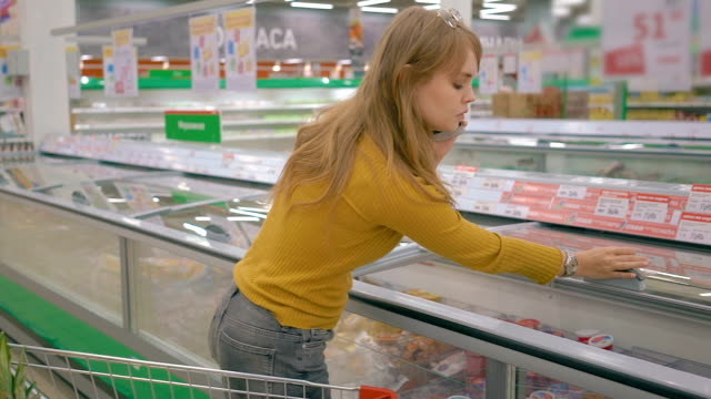Young woman with mobile phone taking product from fridge at supermarket