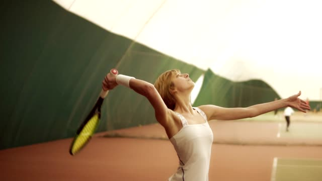 テニスコート、ラケットでボールを打つ白スポーツウェアを着て筋肉ボディを持つ若い女性は。裁判所、屋内を覆われている映像、スロー モーション - テニス点の映像素材/bロール