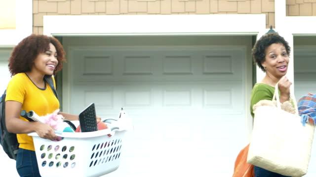 young woman with parents helping her move - odejście filmów i materiałów b-roll