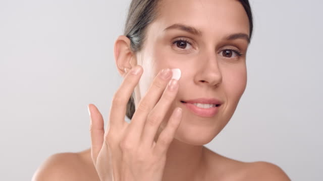 Young woman with perfect skin applies cream on her face video