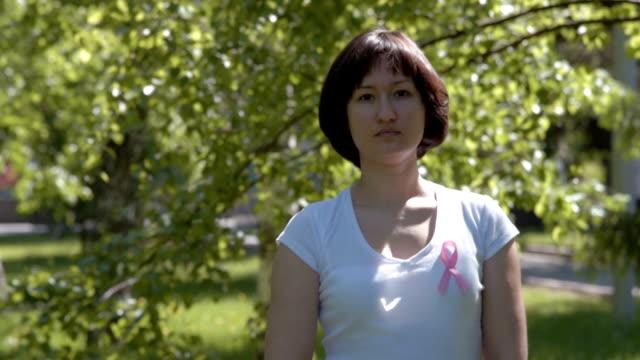 young woman with pink awareness ribbon - breast cancer awareness filmów i materiałów b-roll
