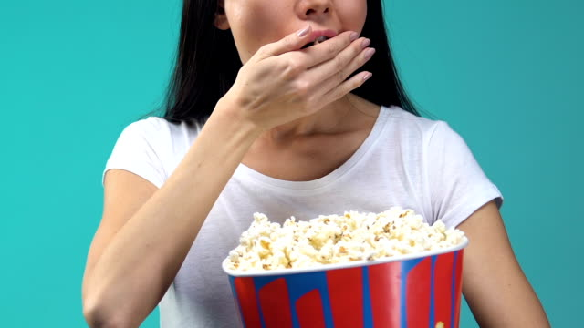 young woman with popcorn attentively watching tv show, overeating, junk food - telecomando background video stock e b–roll