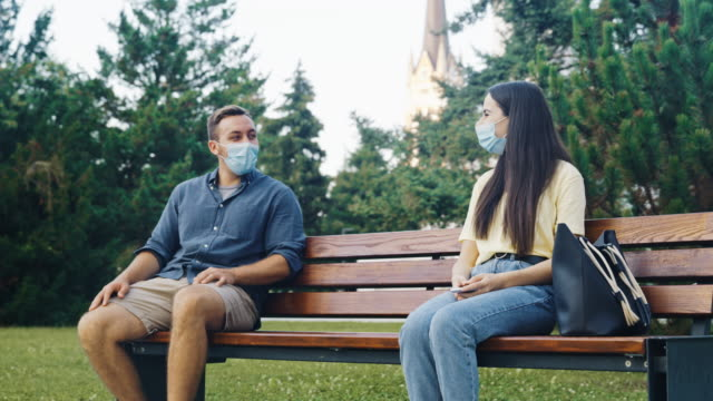 SLO MO Young woman with protective face masks using phone and meeting friend on the bench in public park