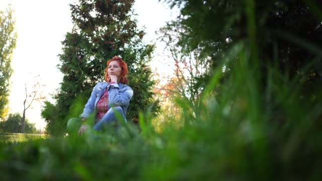 Young woman with red hair among trees. Portrait of young attractive female with trendy hairstyle standing in spring garden and looking at camera Young woman with red hair among trees. dyed red hair stock videos & royalty-free footage
