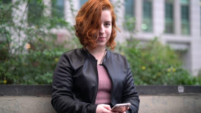молодая женщина с рыжими волосами с помощью мобильного - портрет - бразилец парду стоковые видео и кадры b-roll