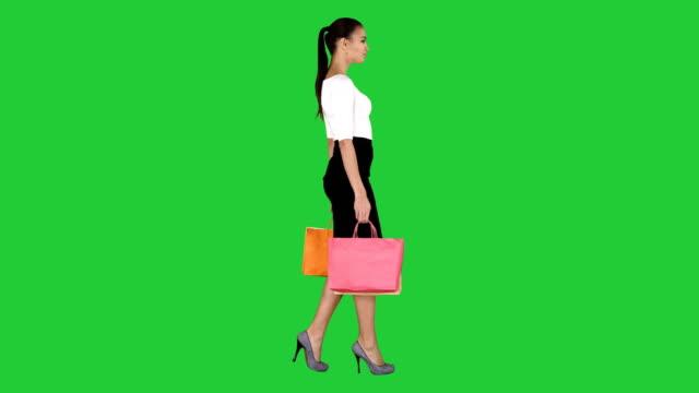 買い物袋を持つ若い女性グリーンスクリーンで買い物をすると、クロマ・キー - 全身点の映像素材/bロール
