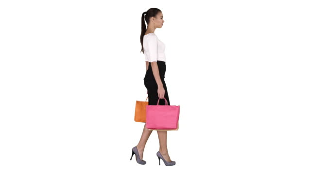 Young woman with shopping bags walking out from shop on white background