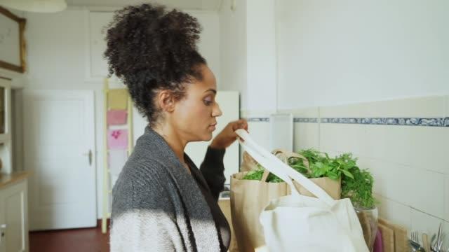 キッチンでのショッピングを持つ若い女性 - 荷物をとく点の映像素材/bロール