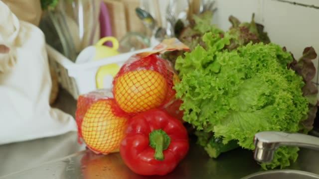 vídeos de stock, filmes e b-roll de mulher jovem com as compras na cozinha - comida feita em casa