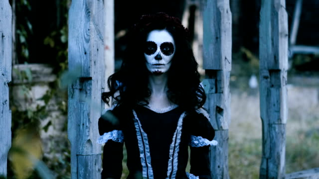 A young woman with skull make-up for Halloween on the background of old house. 4K The Mexican Day of the Dead. The portrait of young woman with scary skeleton make-up for Halloween on the background of wooden old house. 4K skull stock videos & royalty-free footage