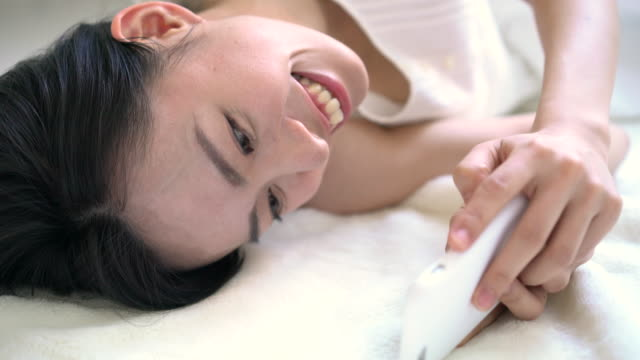 若い女性のスマートフォン - スマホ ベッド点の映像素材/bロール